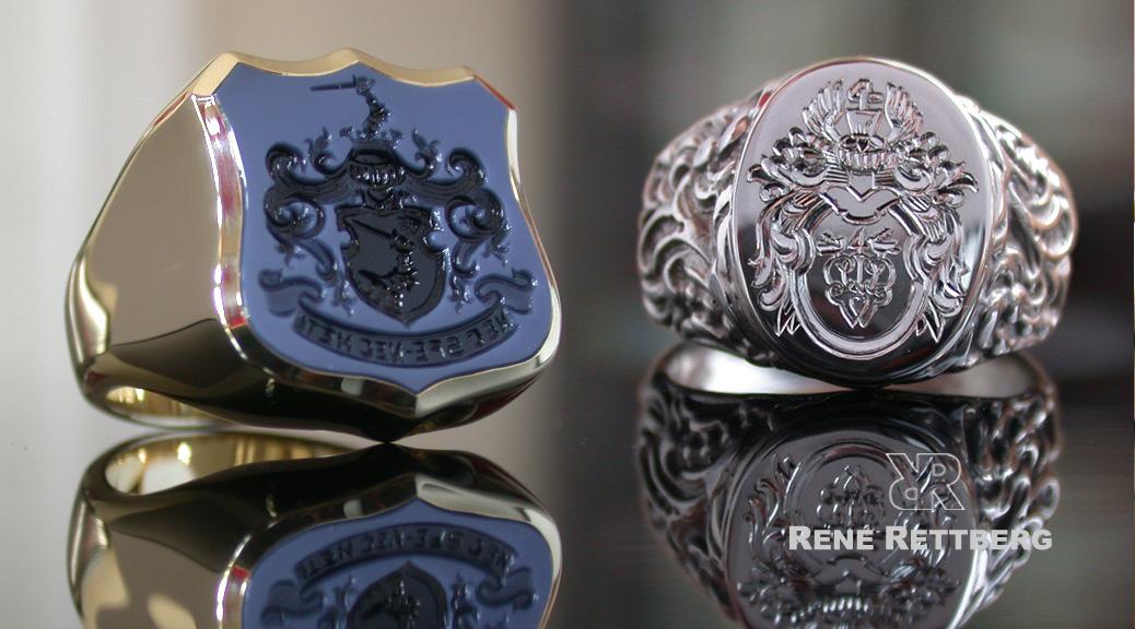 Wappenförmiger Siegelring neben silbernen Ornamentring in barocker Optik
